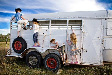 (Left to right) Tyler (age 6),  Frankie (age 5),  Jimmy (age 4) and Brilee (age 4) play on an old horse trailer