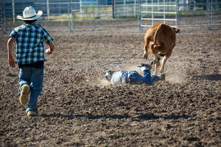 A young man gets thrown off the bull at the youth rodeo
