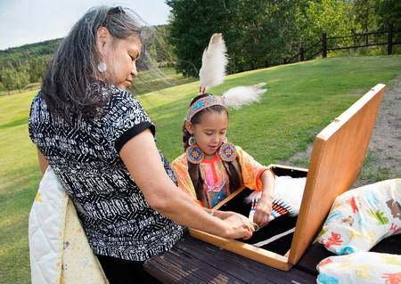 Heather's mother, Carol allows Lanaiya to practice her Blackfeet dance with special Golden Eagle feathers.