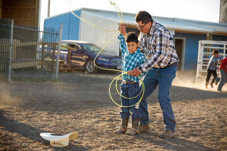 Ethan David helps his son, Josh prepare for the dummy roping competition.